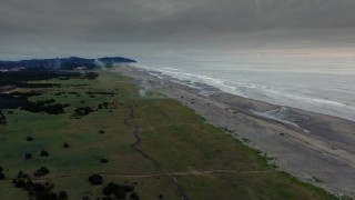 DX0002_148_037 - 4K stock footage aerial video of the beach as fireworks go off at sunset in Long Beach, Washington