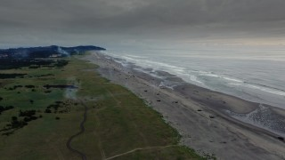 DX0002_148_038 - 4K stock footage aerial video reverse view of the beach as fireworks go off at sunset in Long Beach, Washington