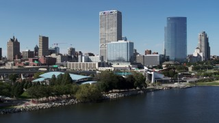 DX0002_149_031 - 5.7K stock footage aerial video of tall skyscrapers seen while flying by a waterfront outdoor stage in Downtown Milwaukee, Wisconsin