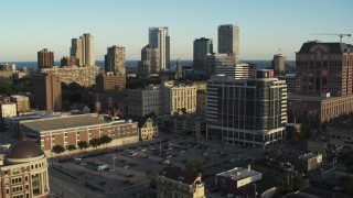 DX0002_150_012 - 5.7K stock footage aerial video of flying by a dormitory complex for view of skyline at sunset in Downtown Milwaukee, Wisconsin
