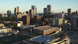 DX0002_150_019 - 5.7K stock footage aerial video of away from the skyline, descend near college campus at sunset in Downtown Milwaukee, Wisconsin