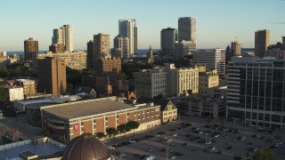 DX0002_150_022 - 5.7K stock footage aerial video ascend away from college campus at sunset with view of city skyline, Downtown Milwaukee, Wisconsin