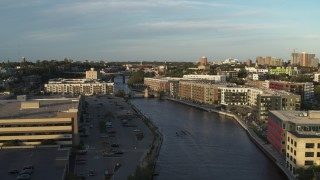 DX0002_150_024 - 5.7K stock footage aerial video ascend past apartment complexes by the Milwaukee River at sunset, Milwaukee, Wisconsin