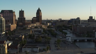 DX0002_150_025 - 5.7K stock footage aerial video tall office tower by the Milwaukee River at sunset, Downtown Milwaukee, Wisconsin