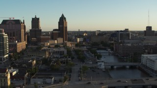 DX0002_150_026 - 5.7K stock footage aerial video tall office tower and city buildings by the Milwaukee River at sunset, Downtown Milwaukee, Wisconsin
