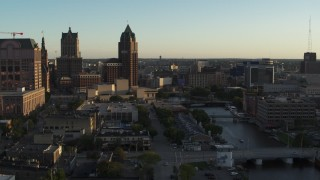 DX0002_150_028 - 5.7K stock footage aerial video view of city buildings, tall office tower by the Milwaukee River at sunset, Downtown Milwaukee, Wisconsin