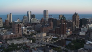 DX0002_150_029 - 5.7K stock footage aerial video city buildings and skyscrapers seen from Milwaukee River at twilight, Downtown Milwaukee, Wisconsin