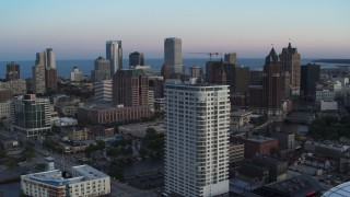 DX0002_150_030 - 5.7K stock footage aerial video descend by apartment complex with view of downtown at twilight, Downtown Milwaukee, Wisconsin