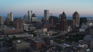 DX0002_150_032 - 5.7K stock footage aerial video city buildings and skyscrapers behind office tower at twilight, Downtown Milwaukee, Wisconsin