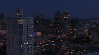 DX0002_151_004 - 5.7K stock footage aerial video descend by apartment high-rise at night with view of office tower, Downtown Milwaukee, Wisconsin