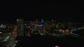 DX0002_151_013 - 5.7K stock footage aerial video pan from a high-rise apartment building at night, focus on skyline, Downtown Milwaukee, Wisconsin