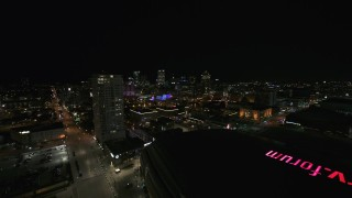 DX0002_151_014 - 5.7K stock footage aerial video reverse view of high-rise apartment building and skyline at night, Downtown Milwaukee, Wisconsin