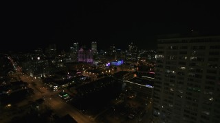 DX0002_151_016 - 5.7K stock footage aerial video fly around apartment high-rise toward city skyline at night, Downtown Milwaukee, Wisconsin
