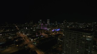 DX0002_151_018 - 5.7K stock footage aerial video fly away from skyline to reveal an apartment high-rise at night, Downtown Milwaukee, Wisconsin