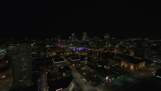 DX0002_151_020 - 5.7K stock footage aerial video reverse view of the city skyline and apartment high-rise at night, Downtown Milwaukee, Wisconsin