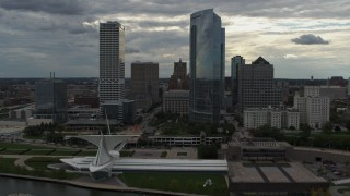 DX0002_154_018 - 5.7K stock footage aerial video ascend toward city's waterfront museum and skyline from the lake in Downtown Milwaukee, Wisconsin