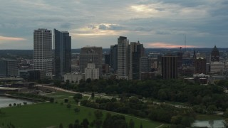 DX0002_155_013 - 5.7K stock footage aerial video of tall skyscrapers in the city's skyline seen from green park at sunset, Downtown Milwaukee, Wisconsin