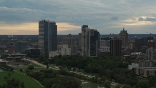 DX0002_155_014 - 5.7K stock footage aerial video view of tall skyscrapers in the city's skyline seen while descending to green park at sunset, Downtown Milwaukee, Wisconsin