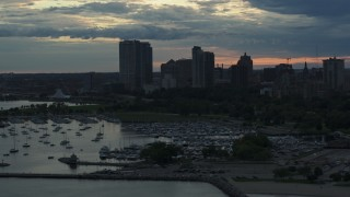 DX0002_155_023 - 5.7K stock footage aerial video of skyscrapers in the city's skyline seen from a marina at sunset, Downtown Milwaukee, Wisconsin