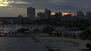 DX0002_155_028 - 5.7K stock footage aerial video of descending by the marina with a view of the city's skyline at twilight, Downtown Milwaukee, Wisconsin