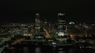 DX0002_157_006 - 5.7K stock footage aerial video of flying away from towering skyscrapers at night, Downtown Milwaukee, Wisconsin