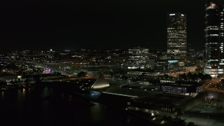 DX0002_157_012 - 5.7K stock footage aerial video fly away from museum and skyscrapers at night, Downtown Milwaukee, Wisconsin