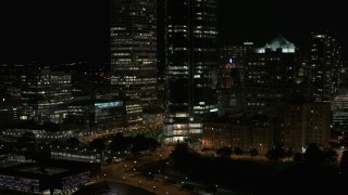 DX0002_157_032 - 5.7K stock footage aerial video of the base of a tall skyscraper at night, Downtown Milwaukee, Wisconsin