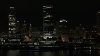 DX0002_157_034 - 5.7K stock footage aerial video of a wide orbit of a towering skyscraper at night, Downtown Milwaukee, Wisconsin
