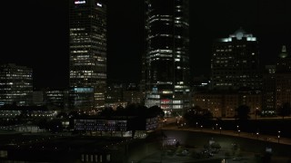 DX0002_157_035 - 5.7K stock footage aerial video orbit base of a towering skyscraper at night, Downtown Milwaukee, Wisconsin
