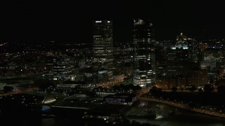 DX0002_157_038 - 5.7K stock footage aerial video fly away from a pair of towering skyscrapers at night, Downtown Milwaukee, Wisconsin