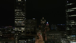 DX0002_157_050 - 5.7K stock footage aerial video reverse view of Wisconsin Avenue and skyscrapers at night, Downtown Milwaukee, Wisconsin