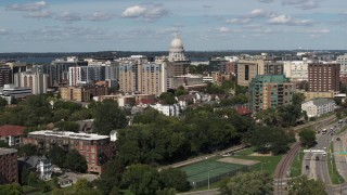 DX0002_158_009 - 5.7K stock footage aerial video flyby and away from apartment buildings and capitol dome in Madison, Wisconsin