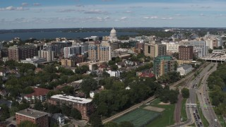 DX0002_158_015 - 5.7K stock footage aerial video ascend over lake with view of of apartment buildings near the capitol dome in Madison, Wisconsin