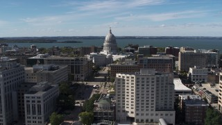 DX0002_158_028 - 5.7K stock footage aerial video of slowly passing the capitol dome surrounded by office buildings, Madison, Wisconsin