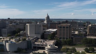 DX0002_158_033 - 5.7K stock footage aerial video flyby the convention center, ascend for view of capitol dome, office buildings, Madison, Wisconsin