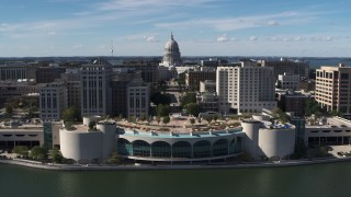 DX0002_158_036 - 5.7K stock footage aerial video of the capitol dome and office buildings, seen while ascending past convention center, Madison, Wisconsin