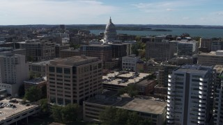 DX0002_158_038 - 5.7K stock footage aerial video of the capitol dome seen while passing office buildings, Madison, Wisconsin