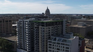 DX0002_158_039 - 5.7K stock footage aerial video of the capitol dome seen while descending by condo complexes, Madison, Wisconsin