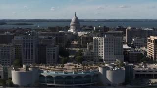 DX0002_160_001 - 5.7K stock footage aerial video of the capitol dome seen while ascending past office buildings, Madison, Wisconsin