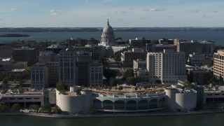 DX0002_160_003 - 5.7K stock footage aerial video of the capitol seen while passing by office buildings and convention center, Madison, Wisconsin
