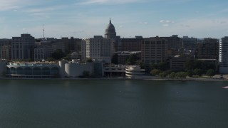 DX0002_160_006 - 5.7K stock footage aerial video dome of the capitol seen while flying away from office buildings and convention center, Madison, Wisconsin