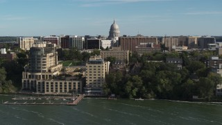 DX0002_160_024 - 5.7K stock footage aerial video focus on the capitol dome while passing lakeside hotel in Madison, Wisconsin