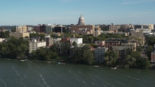 DX0002_160_025 - 5.7K stock footage aerial video focus on the capitol dome while passing lakeside apartment buildings in Madison, Wisconsin