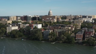 DX0002_160_026 - 5.7K stock footage aerial video focus on the capitol dome while flying away from lakeside apartment buildings in Madison, Wisconsin