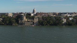 DX0002_160_027 - 5.7K stock footage aerial video focus on the capitol dome while flying past a lakeside hotel in Madison, Wisconsin