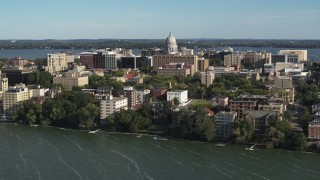 DX0002_160_030 - 5.7K stock footage aerial video reverse view of the capitol dome and lakeside apartment buildings in Madison, Wisconsin