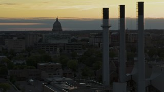 DX0002_161_028 - 5.7K stock footage aerial video flyby the capitol dome at sunset, reveal smoke stacks, Madison, Wisconsin