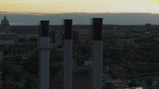 DX0002_161_030 - 5.7K stock footage aerial video passing the capitol dome at sunset, reveal and orbit smoke stacks, Madison, Wisconsin