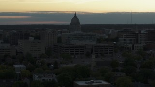 DX0002_161_031 - 5.7K stock footage aerial video approach and flyby the capitol dome at sunset, reveal smoke stacks, Madison, Wisconsin