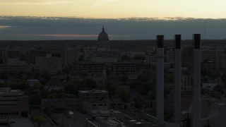 DX0002_162_004 - 5.7K stock footage aerial video flyby smoke stacks to approach the capitol dome at sunset, Madison, Wisconsin